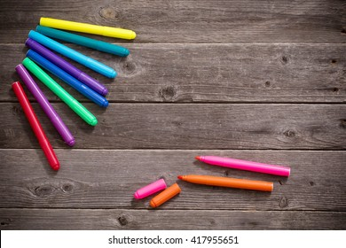 multi-colored felt-tip pens on wooden background