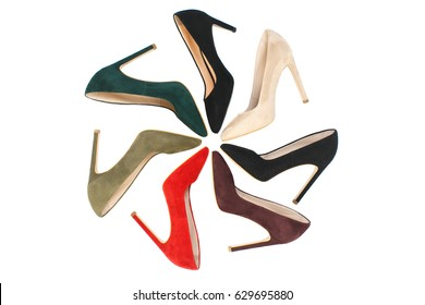 Multicolored female shammy-leather high heels shoes arranged in a circle isolated on white background, women's footwear composition