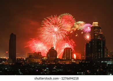 Multicolored firework on sky at night over the skyscraper in downtown Bangkok, the capital city of Thailand in southeast Asia, in horizontal view.