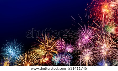 multi colored fireworks as a border on dark blue background ideal for new year