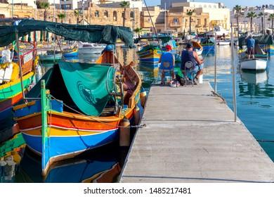 Multicolored fishing boats Luzzu with eyes in the harbor. Marsaxlokk. Malta.