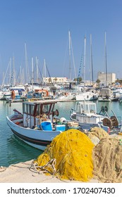 multi-colored fishing nets on the sunny promenade and small fishing boats in the harbor of the Greek village of Sissi