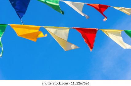Multicolored flags a triangular shape  against the blue sky. Good background on the theme of a city street holiday