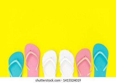 Multicolored  flipflops shoes on yellow background, top view, copy space. Toe sandals, flat lay, text place. Summer background with flipflop shoes