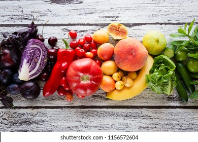 Multicolored fresh fruits and vegetables on a wooden background