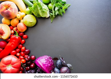 Multicolored fresh fruits and vegetables on a black background with copy space