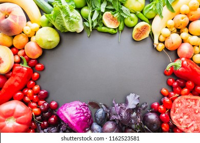 Multicolored fresh fruits and vegetables on a black background, there is a copy space in the center