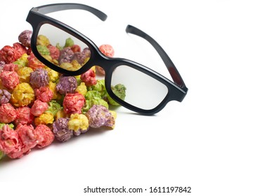 Multicolored fruit flavored popcorn with cinema 3D glasses on pink background. Candy coated popcorn.