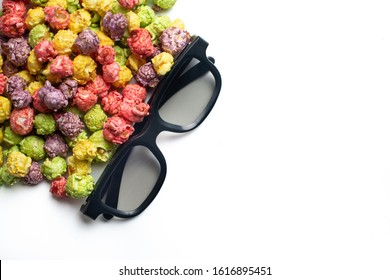 Multicolored fruit flavored popcorn with cinema 3D glasses on pink background. Candy coated popcorn. Top view.