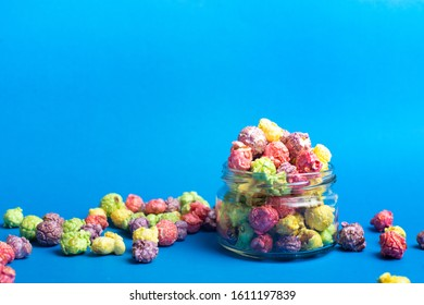Multicolored fruit flavored popcorn in glass cups on blue background. Candy coated popcorn.