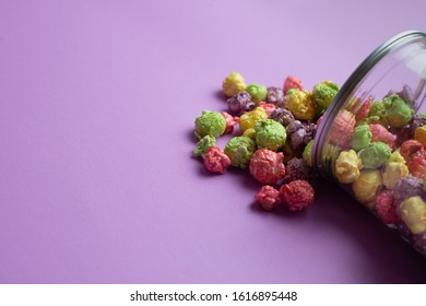 Multicolored fruit flavored popcorn in glass cups on pink background. Candy coated popcorn.