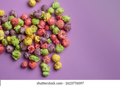 Multicolored fruit flavored popcorn on pink background. Candy coated popcorn.