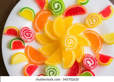 Multicolored fruit jellies on a white plate. Delicious and beautiful dessert.