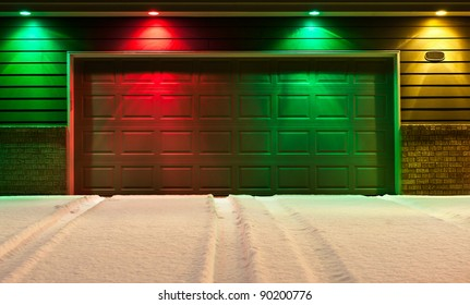 Multi-Colored Garage Door and Snowy Driveway - red, green and yellow lights decorate the front of a garage