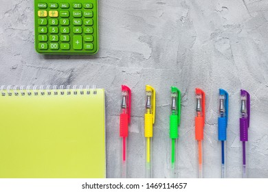 Multicolored gel pens on a gray background. Education, back to school or freelancer concept, flat lay, top view, social media hero header template, copy space.
