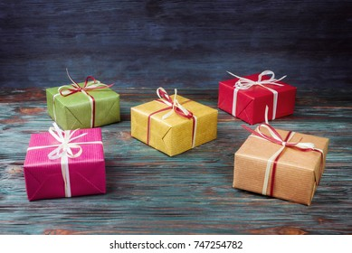 Multicolored gift boxes on wooden background