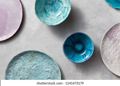 Multi-colored glay vintage handmade dishes. Flat lay. Set of porcelain blue bowls on a gray concrete table.
