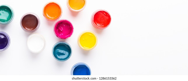 Multicolored gouache on a white background Isolated Paints in containers Top view Copy space Banner Horizontal