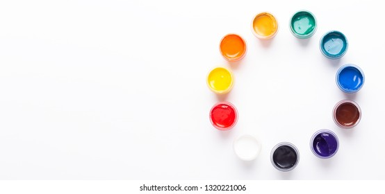 Multicolored gouache on a white background Circle shape Isolated Paints in containers Top view Copy space Banner Horizontal