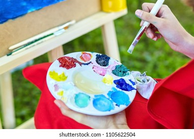 Multicolored gouache paints, brush, palette, female hand of the artist. Plein Air Painting. Development of creative talent