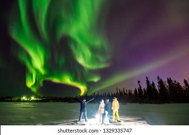Multicolored green Violet vibrant Aurora Borealis Polaris, Northern Lights in night sky over winter Lapland landscape, Norway, Scandinavia. Concept travel team people. Soft focus blur effect