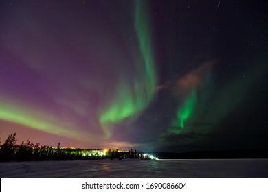 Multicolored green Violet vibrant Aurora Borealis Polaris, Northern Lights in night sky over winter Lapland landscape, Norway, Scandinavia.