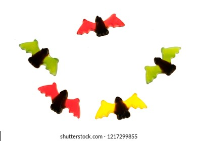 multicolored gummy jelly bat candies over white background