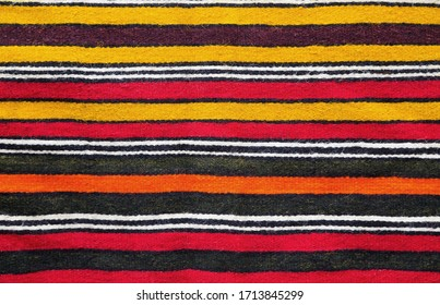 Multicolored handmade woollen rug texture with parallel stripes in red, yellow, black, white and orange in a closeup full frame view