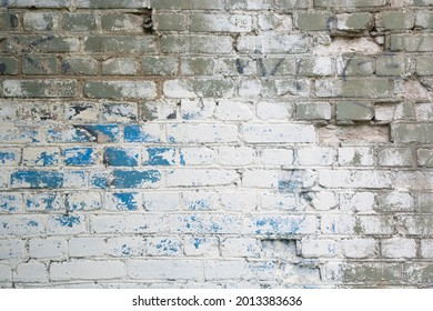 multicolored horizontal aged brick wall with white, gray-green and blue spots