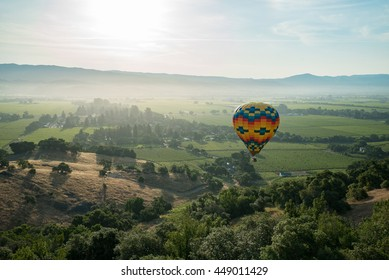 Multicolored hot air balloon float in blue sunny sky near trees over Norther California vineyards