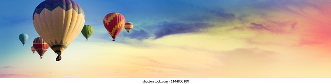 Multicolored hot air balloons at sunset sky for your billboard of a travel agency or wide banner, brigth colors and soft sun light.
