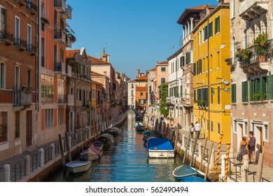 Multicolored houses on both sides of the channel on the background of blue sky