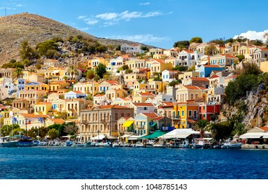 Multi-colored houses on the shore of the bay in the city of Simi on the Greek island of the same name in the Aegean Sea
