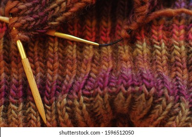 Multi-colored knitwork. knitting needles rib stitch pattern. knitting scarf in ribbed stitches