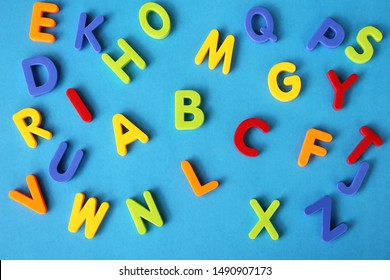Multicolored letters of the English alphabet on a blue background. Learning foreign language. English for beginners.
