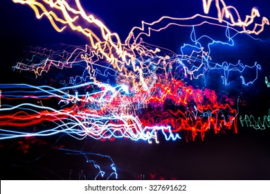 Multicolored light streaks from Neon, Sodium, and LED lights from an Urban street in a modern city. Black background and lightpainting trails create an abstract effect.