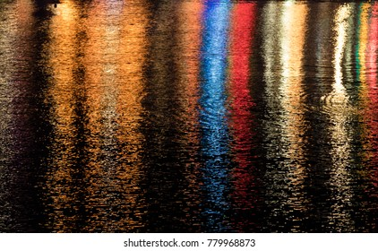 Multicolored lights refected in the water of the harbour in Porthleven Cornwall at night.