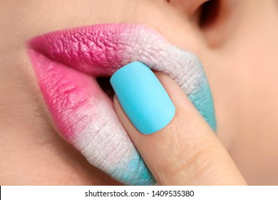 Multi-colored lip makeup and nail design with pink, blue matte and white lacquer with different forms of nails. Manicure close-up.