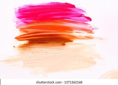 Multicolored lipstic smudge white isolated background.Red brown orange lipstic smudge.