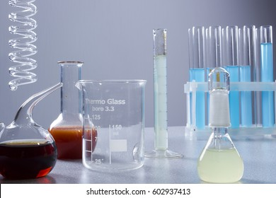 Multicolored liquids in laboratory glassware on a gray background