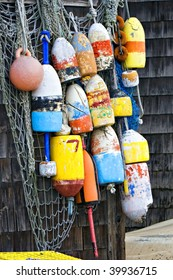 multi-colored Lobster Buoys hanging on cedar shingle wall with  rope, twine and string.