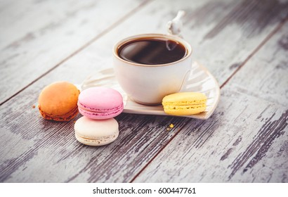 multicolored macaroon cookies and white coffe cup on a wooden table. Photo toned with vignette