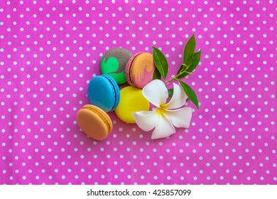 Multicolored macaroon different lie on the pink fabric with the frangipani flower  with the top view