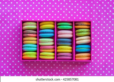 Multicolored macaroon different lie in the pink cardboard box with the top view on the pink fabric