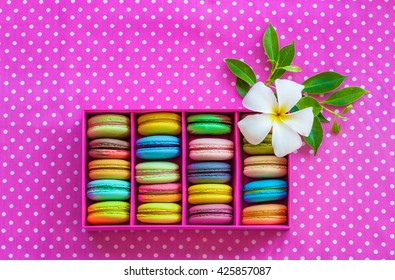 Multicolored macaroon different lie in the pink cardboard box with the frangipani flower  with the top view on the pink fabric