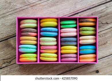 Multicolored macaroon different lie in the pink cardboard box with the top view on the old wooden table