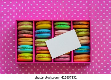 Multicolored macaroon different lie in the pink cardboard box with the business card with the top view on the old wooden table
