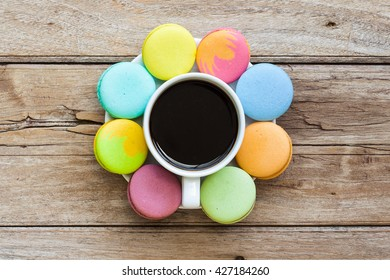 Multicolored macaroon different lie in the saucer with coffee with the top view on the old wooden table