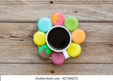 Multicolored macaroon different lie in the saucer with cafe with the top view on the old wooden table