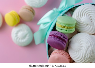 Multicolored macaroons or macarons in a turquoise box with a space for text on pastel pink background. Greeting or invitation card concept.